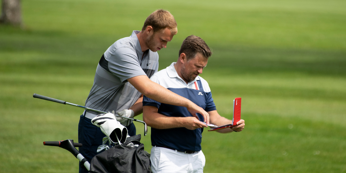 Two players looking at a scorecard