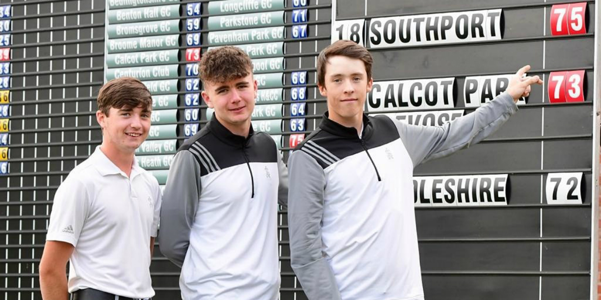 Ellis Willmott, Bradley Smith and George Carrington stand in front of the English Junior Champion Club Leaderboard